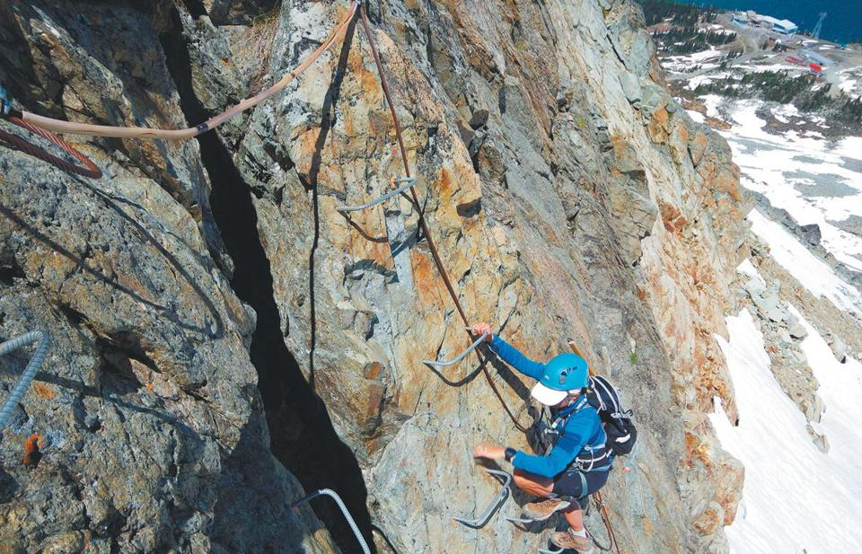 The author uses rebar steps, carabiners, and fixed cables to climb a wall on Whistler's Via Ferrata (Iron Road).